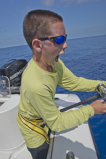 Young boy reeling in a big fish in Key West on a charter.